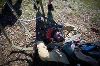 A smokejumper rests after being dropped from 'The Mutilator', a mechanized pulley system that picks smokejumpers up off the ground and drops them repeatedly.