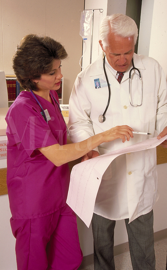 Doctor and nurse review patient chart at hospital