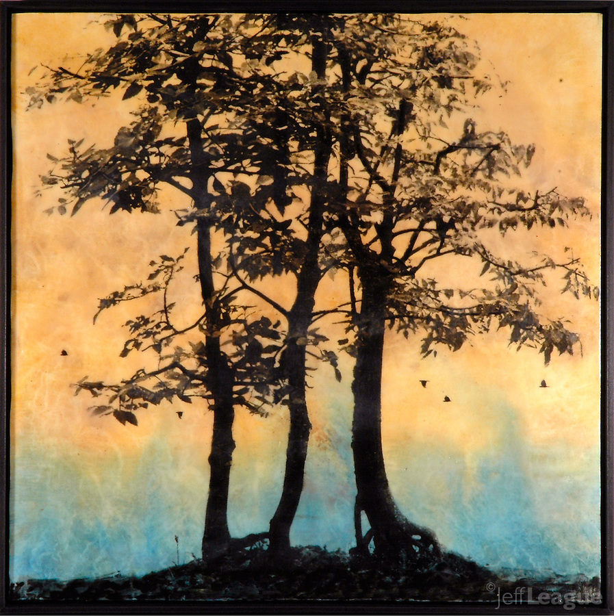 Mixed media encaustic photo painting of trees silhouetted against yellow and cerulean sky.