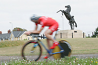 05 MAY 2007 - STETCHWORTH, UK - A competitor races past a statue of a horse and stable lad beside an entrance of Newmarket Racecourse during the BUSA 25 Mile Time Trial Championships. (PHOTO (C) NIGEL FARROW)