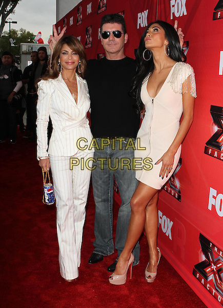 "Paula Abdul, Simon Cowell and Nicole Scherzinger.FOX's ""The X Factor"" Press Conference held at CBS Television City, Los Angeles, California, USA..December 19th, 2011.full length black top white cream dress jeans denim cleavage low cut neckline zip zipper sunglasses shades suit pinstripe jacket trousers pepsi can bag purse blue  hands fingers bunny ears looking up .CAP/ADM/KB.©Kevan Brooks/AdMedia/Capital Pictures."