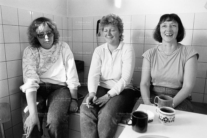 Switzerland. Canton Bern. Frutigen. Blue collar workers take a break, smoke a cigarette and drink coffee.  Two women are happy, one is sad. © 1988 Didier Ruef