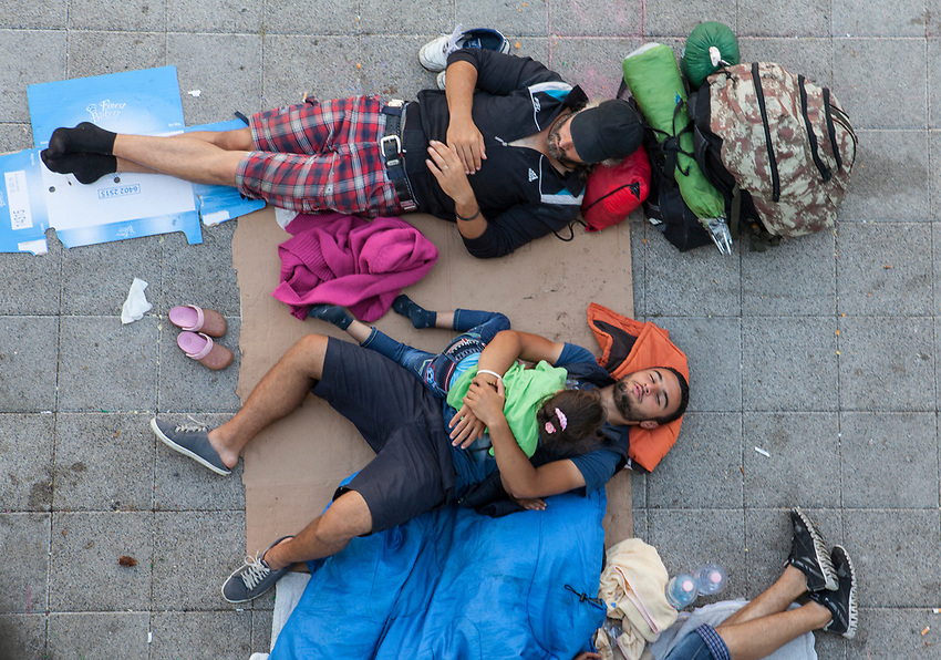 A man cradles his daughter while he sleeps on the pavement outside the station. Mostly Syrian refugees seek rest while waiting for trains to take them away to destinations around Europe. The Hungarian government closed the station and then reopened but cancelled all international trains. Budapest Keleti railway station  is the main international and inter-city railway terminal in Budapest, Hungary.