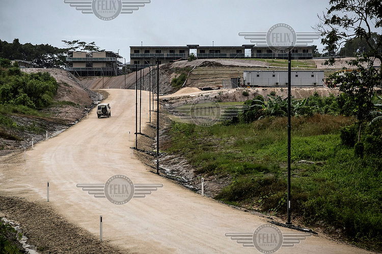 A security vehicle drives down a road leading to the accommodation buildings for the refugees on Manus Island.