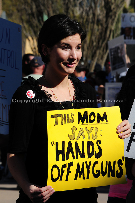 "Phoenix, Arizona. January 19, 2013 - A protester who attended Saturday's rally in Phoenix opposes the president's proposed changes to gun laws in America by holding a sign that reads: ""This mom says: hands off my guns."" As President Barack Obama proposed new gun regulations last week, gun owners demonstrated against it with national ""Guns Across America"" rallies to defend the Second Amendment. Dozens showed up at the Arizona State Capitol, many of them carrying weapons. Photo by Eduardo Barraza © 2013"