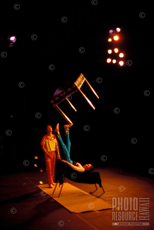 Chinese acrobatic act, girl lying on back balancing an upright table on her foot