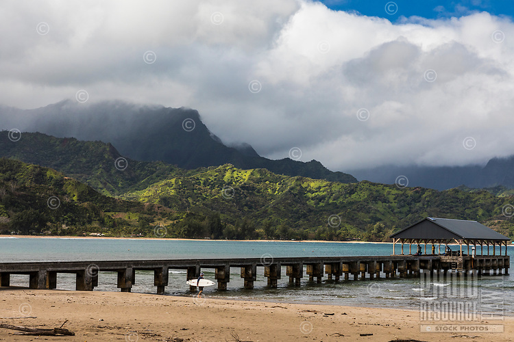 A surfer heads into Hanalei Bay, center, while others enjoy the view from Hanalei Pier, Kaua'i.