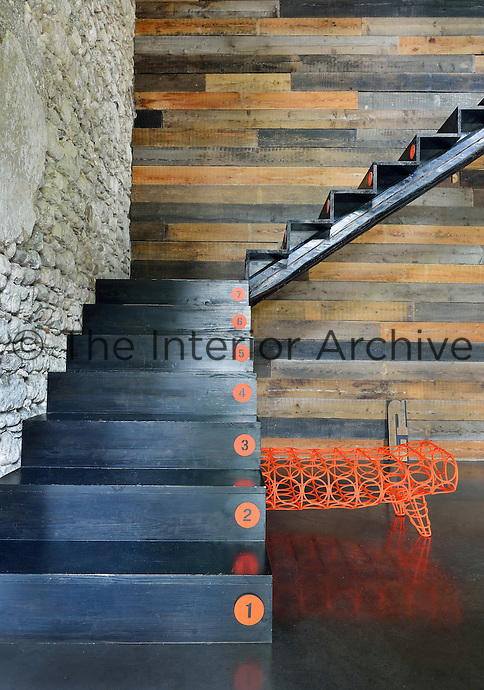 A contemporary staircase hallway with functional steps leading to the upper floor set against a wood clad wall.