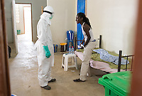 Patient Monique Meating gets a closer look at a photo of health care worker Jerry Kollie on his PPE (personal protective equipment) at ELWA II's Ebola treatment unit (ETU) in Monrovia, Liberia on Sunday, March 1, 2015. Meating is suspected of having Ebola and is waiting on her test results. Meating saw Kollie's photo, smiled and said that she recognized him from town.<br /> The photo of Kollie was created by Occidental College professor Mary Beth Heffernan as part of her PPE Portrait Project, which involves photographing health care workers and making disposable, adhesive prints of their images which are then placed on the worker's PPE.<br /> ELWA II has one of the largest numbers of Ebola patients in Liberia at the moment and was the first ETU to open in Monrovia, Liberia's capital city.<br /> (Photo by Marc Campos, Occidental College Photographer) Mary Beth Heffernan, professor of art and art history at Occidental College, works in Monrovia the capital of Liberia, Africa in 2015. Professor Heffernan was there to work on her PPE (personal protective equipment) Portrait Project, which helps health care workers and patients fighting the Ebola virus disease in West Africa.<br />