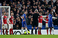 The crowd, Arsenal players and Chelsea players anxiously await a decision from referee, Martin Atkinson, as he listens to the VAR team on his earpiece during Chelsea vs Arsenal, Caraboa Cup Football at Stamford Bridge on 10th January 2018