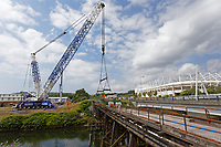 Pictured: A crane prepares to lift the Bascule Bridge over river Tawe in the Morfa area of Swansea, south Wales. Sunday 14 July 2019<br /> Re: A 110 year old bridge has been moved for restoration in Swansea, Wales, UK.<br /> Preparation work has been under way for weeks and the Bascule Bridge near the Liberty Stadium has been lifted by a crane, in one piece.<br /> It took more than 20 workers, a 53m (174ft) crane and and a truck to complete the manoeuvre.<br /> The 70-tonne Grade II listed bridge will then be assessed and restored at Afon Engineering in Swansea Vale, and re-installed next year.<br /> The bridge was pivotal to the area's time as the world copper capital, and its hinged steel structure would lift to allow for river traffic to pass through.