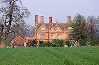 The brick walls of this Jacobean house glow pink in the afternoon sun