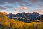 Uncompahgre National Forest, Colorado: Cliffs of the Cimarron stand above fall colored hillside in sunset light; San Juan Mountains
