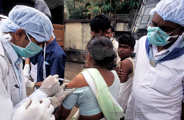 Doctors administering vaccinations to prevent the spread of disease amongst victims of the tsunami which struck South Asia on 26/12/2004..An underwater earthquake measuring 9 on the Richter scale triggered a series of tidal waves which caused devastation when they struck dry land. 12 countries were affected by the tsunami, with a combined death toll of over 150,000.