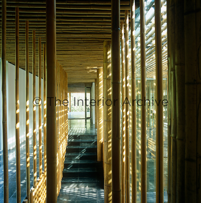 View along a corridor with a dark slate floor and bamboo screens and ceiling
