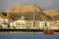 Mutrah, Oman.  An Arab dhow and traditional waterfront architecture denote the harbor of Mutrah, commercial port for Oman's capital, Muscat.  Oman is the legendary home of Sindbad the Sailor.  Behind the town are chocolate-brown ophiolites, a metamorphic, igneous rock.  Compare to Mar72_Oman_37, taken February 1972, at end of this gallery.
