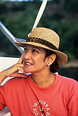 Rio de Janeiro, Brazil. Wealthy woman in a red t-shirt wearing gold ring, ear-rings and bracelet and a straw hat.