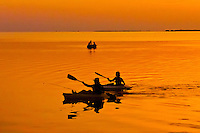 Kayakers off of the Kona Kai resort at sunset, Key Largo, Florida Keys, Florida USA