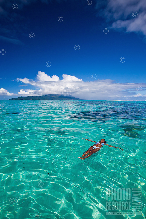 Young woman swimming in  crystal clear lagoon