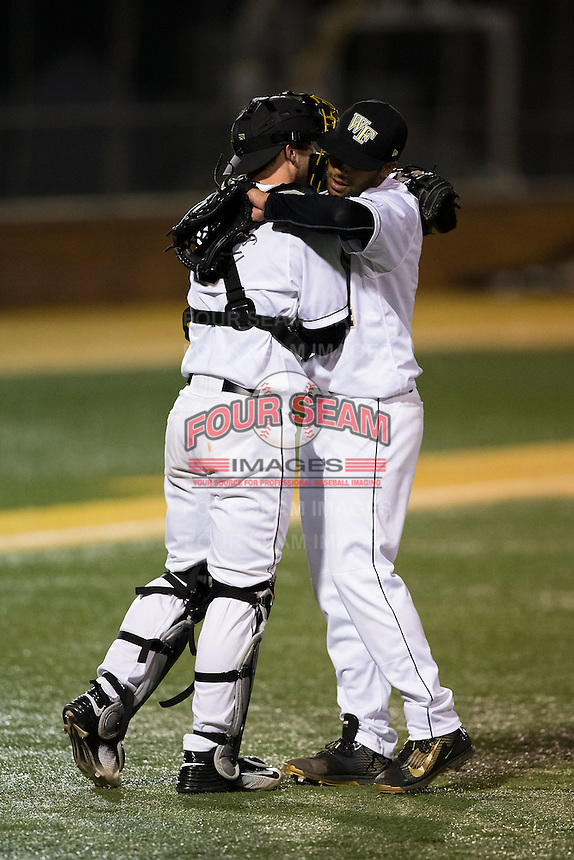Wake Forest Demon Deacons closer Donnie Sellers (right) gets a hug from catcher Ben Breazeale (9) after getting the final out against the Georgetown Hoyas at David F. Couch Ballpark on February 19, 2016 in Winston-Salem, North Carolina.  The Demon Deacons defeated the Hoyas 3-1.  (Brian Westerholt/Four Seam Images)