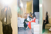Politico reporter Hadas Gold (center right) and Chris Hooton sit in a lounge area toward the end of the night at the MSNBC After Party at the United States Institute of Peace in Washington, DC. Reflected in a golden panel at right, DNC worker Jenna Price and Capitol Hill worker Michael Hardaway also sit in the lounge. At left, photographer M. Scott Brauer can be seen reflected, as well. The party followed the annual White House Correspondents Association Dinner on Saturday, April 30, 2016. The party continued until about 3 AM on Sunday, May 1, 2016.