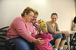 (L-r) Rebecca Bird, 41, with her future wife, Sandra Quandt, 48, and their witness, Rebecca's sister, Jamie Lee (far right), 28, and niece, Shelbie Stevens (in Rebecca's hands), 3, all from Davenport, Iowa, wait while Rebecca and Sandra wait for a marriage license at the Scott County Recorder's Office the first day same sex weddings are legal across Iowa in Davenport, Iowa on April 27, 2009.