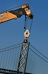 A crane seem to be holding up a tower if of the Oakland Bay Bridge, California.