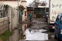 Roma 22  Febbraio 2010.Idroscalo di Ostia.Una donna  raccoglie il fango davanti alla sua abitazione