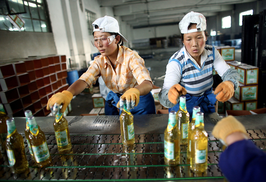 Lhasa Beer factory workers pack bottles for shipping.