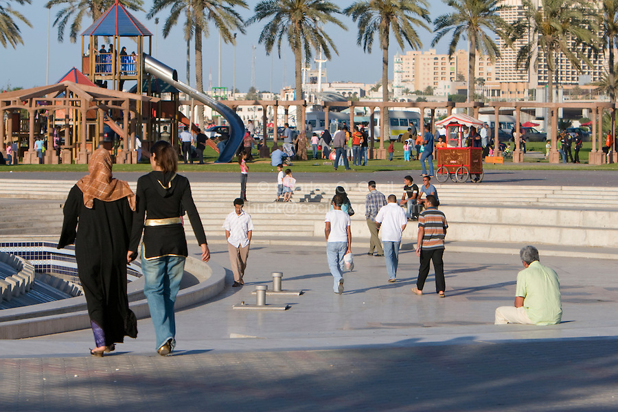 Tripoli, Libya, North Africa - Friday Afternoon in the Public Park, Playground, near the Green Square.  Popcorn Vendor right of center, Children's Slide in left Background, traditional and Western women's dress styles side-by-side.  Young men in western European style clothing.