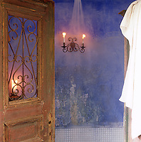 A wooden door with a wrought iron panel opens into at blue painted room with a candle sconce.