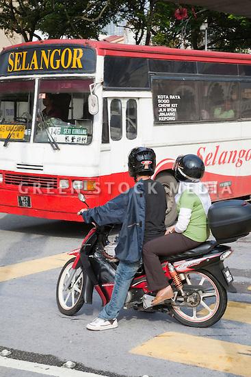 Two people on a moped giving way to a city bus in downtown Kuala Lumpur. Kuala Lumpur, Selangor, Malaysia