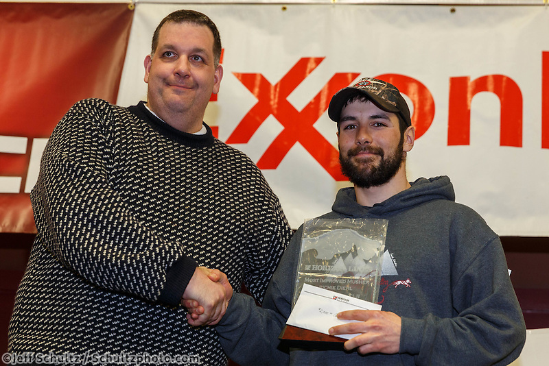 Kenny Gill presents the Horizon Lines Most Improved Musher Award to Richie Diehl at the musher 's finishers banquet in Nome on Sunday March 16 after the 2014 Iditarod Sled Dog Race.<br /> <br /> PHOTO (c) BY JEFF SCHULTZ/IditarodPhotos.com -- REPRODUCTION PROHIBITED WITHOUT PERMISSION
