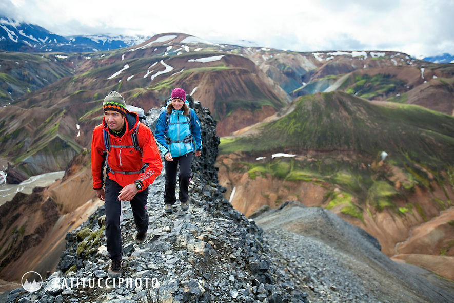 Two hikers in the Landmannalaugar area of Iceland trekking amongst the unique landscape