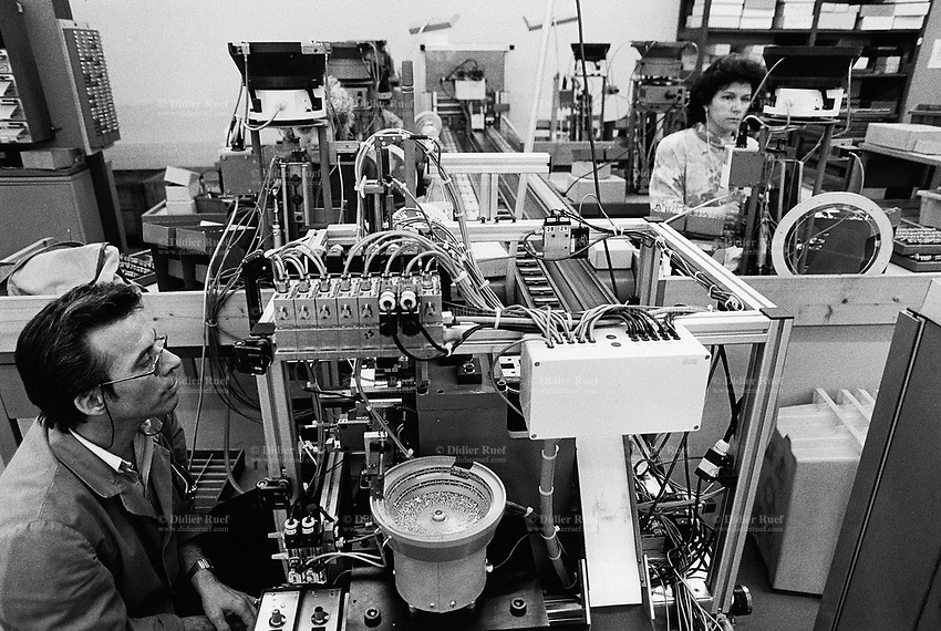 "Switzerland. Canton Jura. Delémont. Wenger SA is a factory where is manufactured the famous swiss army knife. A man checks the good machine's functioning while two women workers assemble by hand the knifes. Wenger is one of two companies that have manufactured Swiss Army knives. Based in Delémont, Wenger was acquired by rival Victorinox in 2005. Since 2013, Wenger Swiss Army knives are integrated in the Victorinox collection (as the ""Delémont collection""). © 1992 Didier Ruef"