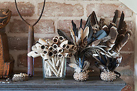 The mantelpiece is decorated with bouquets made from bunches of feathers held in small ornate metal containers and old clay pipes in a simple glass vase