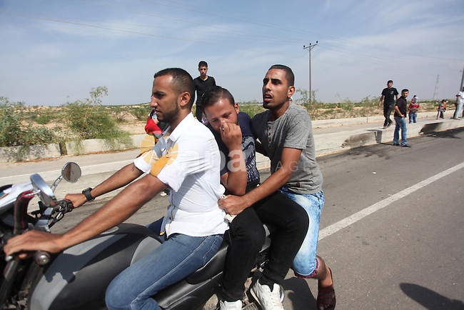 Palestinian protesters carry an injured comrade on a motorcycle during clashes with Israeli security forces next to the border fence with Israel, at the Erez crossing in the northern Gaza strip, on October 13, 2015. A wave of stabbings that hit Israel, Jerusalem and the West Bank this month along with violent protests in annexed east Jerusalem and the occupied West Bank, has led to warnings that a full-scale Palestinian uprising, or third intifada, could erupt. The unrest has also spread to the Gaza Strip, with clashes along the border in recent days leaving nine Palestinians dead from Israeli fire. Photo by Ashraf Amra
