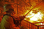 An El Centro firefighter works to save a home along Circle View Drive as wildfires rage in Running Springs near Lake Arrowhead early Tuesday morning October 23, 2007.