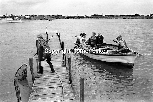 Ferryman rowing travellers from Southwold across the river Blyth to Walberswick Suffolk. UK. 1984.