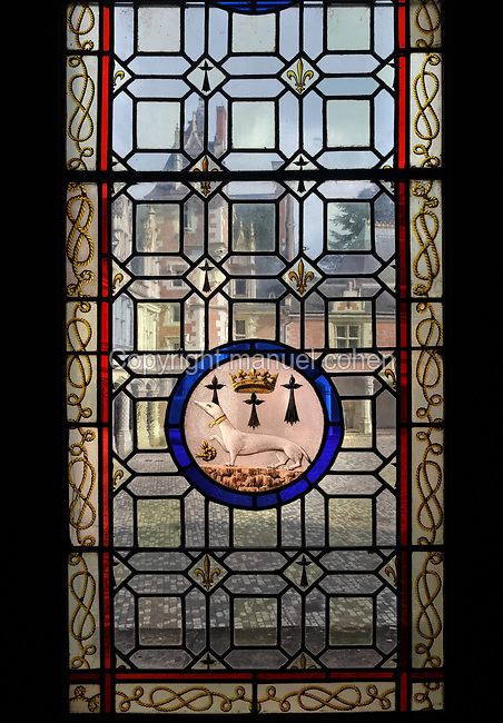 Mullioned stained glass window, 15th century, with additional panel made 1861-66 by Felix Duban featuring an ermine, symbol of Anne of Brittany, wife of Louis XII, in the Salle des Etats Generaux, or Estates General Room, built in 1214 in Gothic style under Thibaut VI, Count of Blois-Champagne, in the Chateau Royal de Blois, built 13th - 17th century in Blois in the Loire Valley, Loir-et-Cher, Centre, France. The large hall is covered by a wooden frame forming 2 naves, supported by 6 arches on 5 columns. In 1861-66 Felix Duban restored the room in Neo-Gothic style, painting the vaulted ceiling with a fleur de lys design. The hall is named after the 2 Estates General of Blois in 1576 and 1588, called by Henri III. The chateau has 564 rooms and 75 staircases and is listed as a historic monument and UNESCO World Heritage Site. Picture by Manuel Cohen
