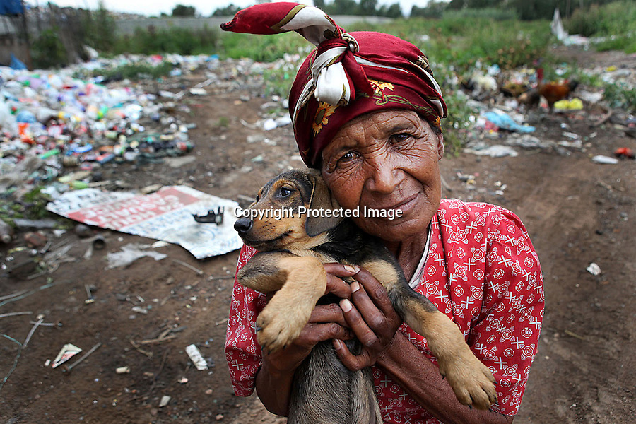 A woman is photographed with her puppy at the Randfontein Refuse Center on the outskirts of Johannesburg, South Africa.  She, like many others, lives in a small shanty and survives off the refuse brought in every day. Many residents sort and sell recyclable items and live off what edible food they can find thrown out by others.