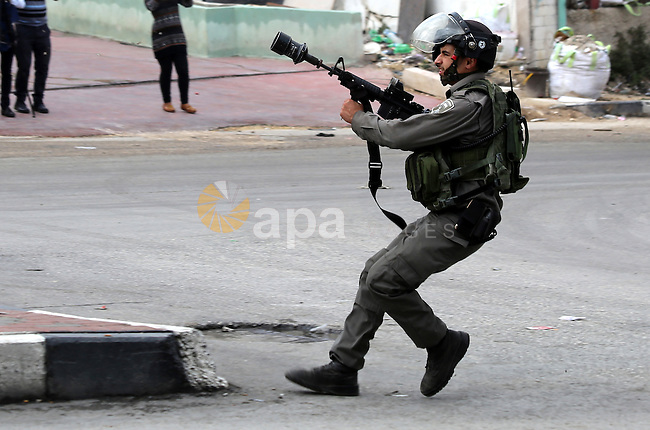 An Israeli soldier fires tear gas at Palestinian protesters during clashes in the village of Beit Ummar near the southern West Bank city of Hebron on October 8, 2015. There have been at least eight stabbing attacks since the beginning of the month, when a Palestinian killed two Israelis in Jerusalem's Old City, helping to prompt a security crackdown and spread riots. Photo by Muhesen Amren