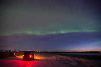 A motorists watches as the aurora borealis, or northern lights, draw a line in the sky above the Kenai, Alaska shortly before sunrise.