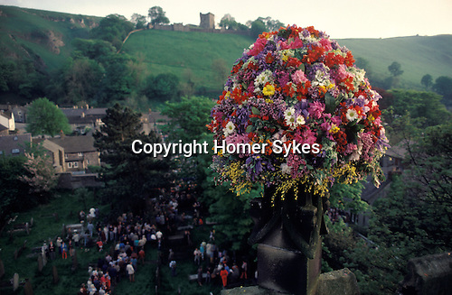 Castleton Garland Day Derbyshire UK. Flowers on top of church tower. Castleton Castle in distance. May 29th UK