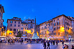 As evening falls the lights come on, the bars around the plaza open, and tourists mix with locals around the central fountain (the Fontana del Pantheo) in the Piazza della Rotonda, in front of the Pantheon in Rome, Italy.