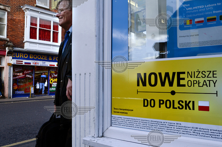 Eastern European brand names dominate a shop window opposite a money transfer shop on West Street in Boston, Lincolnshire. Renamed by locals as 'East Street' this busy shopping area is home to a large number of outlets catering to the large eastern European communitiesin the town, including Polish supermarkets and restaurants. Large migrant European communities live locally and work in the agriculture, horticulture or service sectors, including those catering to their own communities needs.