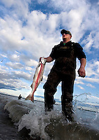 Cory Jackson, of Eagle River, Alaska, washes a sockeye salmon in the Kenai River after catching it with a dipnet. Sockeye salmon are commonly called red salmon in Alaska. While it is possible to take a chinook (or king) salmon with a dipnet, and every other year a strong return of pink salmon show up, reds are the fish Alaskans flock to catch in the river's mouth in Kenai, Alaska.