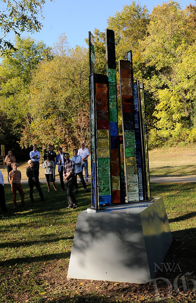 STAFF PHOTO FLIP PUTTHOFF <br /> ART TRAIL<br /> Dayton Castleman, third from right, talks about the trailside stained-glass sculpture, Ozarks Topopgraphy, S4R9T149, on Tuesday Oct. 21 2014 along the North Bentonville Trail. It is one of three sculptures celebrated by art enthusiasts and city officials during a walking tour along the trail Tuesday evening. The Bentonville Public Art Advisory Committee funded the three works. Others are SunKissed, which is a metal work of radiating spokes, and PAC-Man, a stone sculpture that depicts a person hiking. Ed Pennebaker of Osage, creator of Ozarks Topography, S4R9T149, is seen at foreground left.