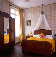 A traditional bedroom with a yellow and blue, floral pattern wallpaper. A wooden bedstead has a sheer curtain canopy and a vibrant yellow cover. A free-standing wardrobe stands against one wall.