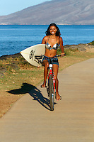 A beautiful, healthy young woman rides a bicycle while carrying a surfboard in Kihei, Maui.